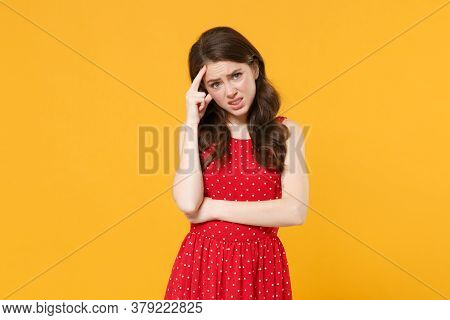 Preoccupied Puzzled Young Brunette Woman Girl In Red Summer Dress Posing Isolated On Yellow Backgrou