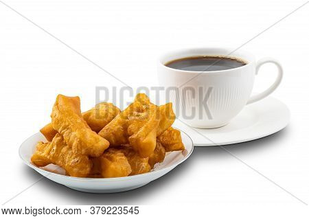 Pile Of Deep-fried Dough Stick In A White Ceramic Plate And Hot Black Coffee In A White Ceramic Cup