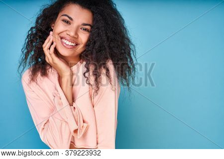 A Joyful Emotional Dark-skinned Lady With Curly Hair, Laughs With Pleasure, Expresses Sincere Emotio