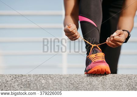 Start Of Day And Workout. African American Girl With Fitness Tracker In Trendy Sportswear Tying Shoe