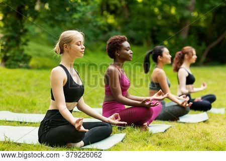 Concentrated Multinational Women Deep In Meditation During Outdoor Yoga Class At Park, Free Space