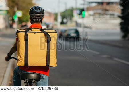City Traffic And Bicycle Delivery Service. Courier In Safety Helmet, Yellow Bag, Rides On Bicycle On