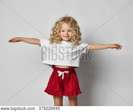 Beautiful Positive Little Blonde Girl With Curly Hair In Stylish Casual Clothing, Sandals And Hat St