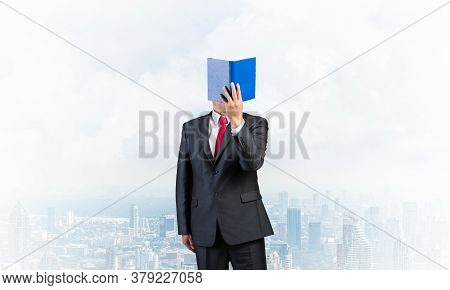 Businessman Covered His Face With Paper Organizer. Man In Business Suit And Tie Standing On Cloudy C