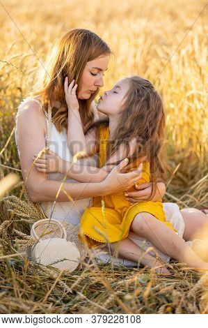 Beautiful Young Mother And Her Daughter At The Wheat Field In Sunny Day In Czech Republic