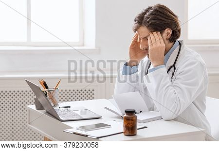 Professional Stress. Overworked Male Doctor Suffering From Headache At Workplace, Empty Space