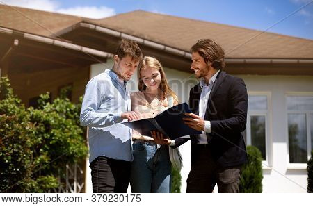 Millennial Couple And Realtor Looking Through House Ownership Documents Near Residential Building Ou