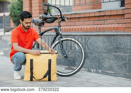 Accurate Delivery. Busy Bearded Courier Zips Up Large Yellow Bag For Client, Beside A Bicycle On Str