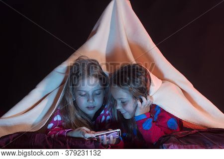 Girls With Interested Faces Lie Under Blanket On Black Background.