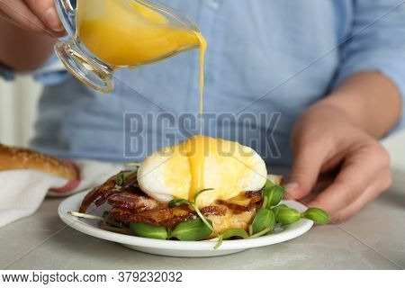 Woman Pouring Hollandaise Sauce Onto Egg Benedict At Table, Closeup