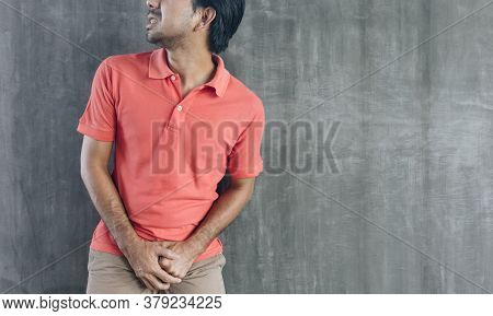 Young Asian Holding His Crotch On Cement Wall Background, Problems And Health Care Concepts, Urinary