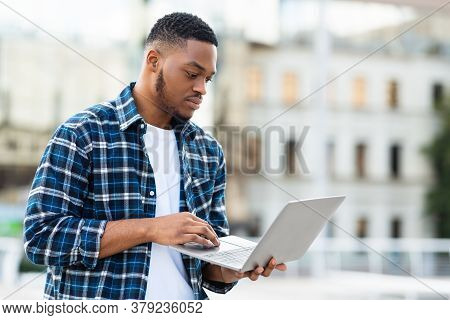 Information And Technology Concept. Focused African Guy Holding Laptop Outdoors, Selective Focus