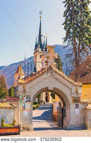Brasov, Romania - March 24, 2015: The Entrance Gate And Saint Nicholas Or Sf. Nicolae Church In Tran