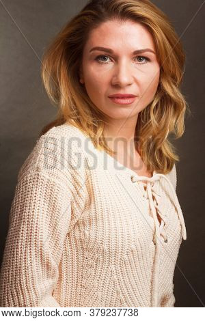 Portrait Of A Middle Aged Blonde Woman In White Clothes On Light Gray Background.