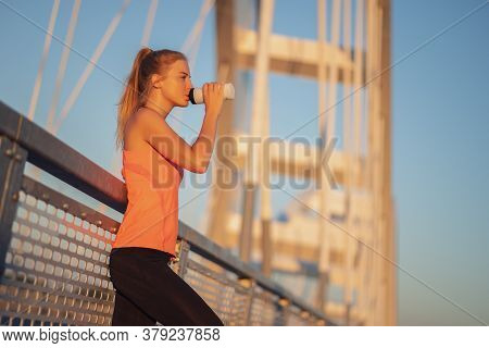 Young Woman Is Exercising Outdoor On Bridge In The City. She Is Drinking Water.