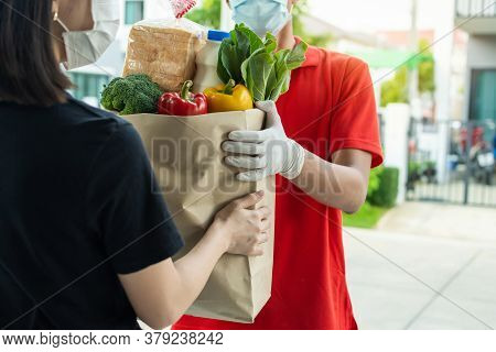 Food Delivery Service Man In Red Uniform Wearing Protection Face Mask Holding Fresh Food Set Bag To