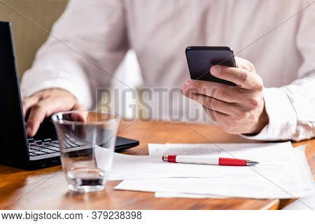 Businessman Using Cell Phone. Businessman Looking At Cell Phone Message. Business Man Watching Cell