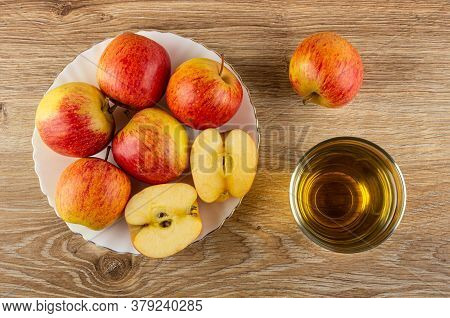 Whole Red Striped Apples And Halves Of Apple In White Plate, Glass Of Apple Juice On Brown Wooden Ta