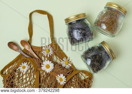 Flat Lay Of Three Glass Jars With Tea, Wooden Spoons And A Reusable String Bag On A Mint Background
