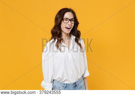 Cheerful Blinking Young Brunette Business Woman In White Shirt Glasses Isolated On Yellow Background