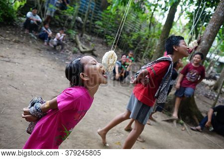 Yogyakarta, Indonesia - August 17, 2019: Indonesian Children Eating Crackers Competition In The Vill