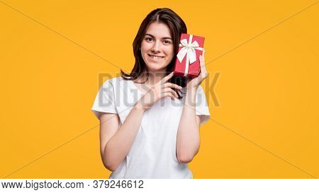 Holiday Present. Birthday Surprise. Happy Cheerful Woman In White T-shirt Holding Red Gift Box Isola