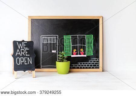 House Drawing On Blackboard, Plant In Pot And We Are Open Word On Chalkboard. Open Singboard Near Ho