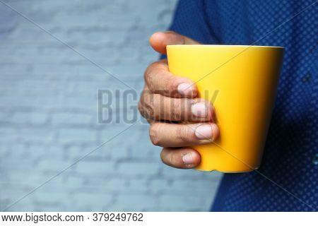 Close Up Of Man Hand Holding Mug Isolated On White