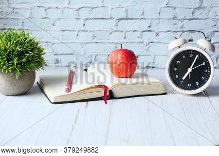 Black To School Concept With Apple On Notepad On Table.