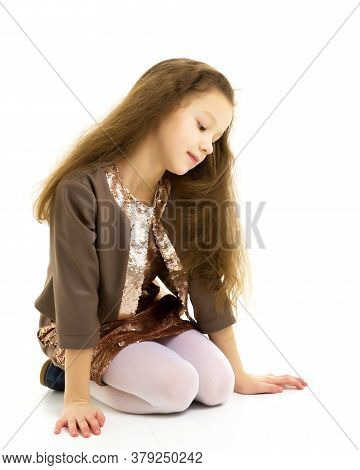 Beautiful Girl Sitting On The Floor On Her Knees, Thoughtful Child Wearing A Summer Dress, Portrait