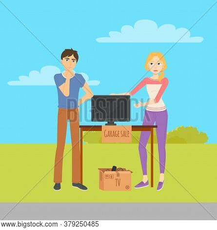 Young Man And Woman Selling Tv Monitor At Garage Sale. Used House Appliances In Cardboard Boxes On W