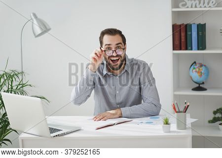 Amazed Young Bearded Business Man In Gray Shirt Glasses Sit At Desk Work On Laptop Pc Computer In Li