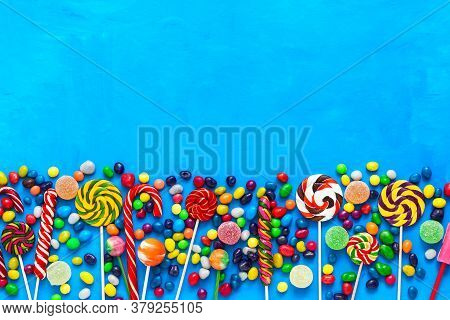 Border Of Multicolored Candies, Round Colorful Candy And Jelly On A Blue Background. Top View, Flat