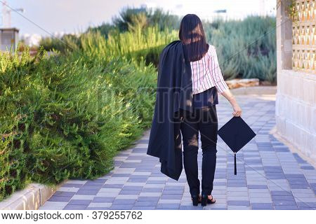 Rear View Of Graduating Student Standing Against City Background. College Young Woman Student At Gra