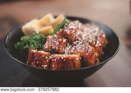 Broiled Eel On Rice In Black Bowl. Japanese Unagi Cuisine
