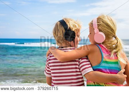 Young Positive Kids In Headphones Listening Music With Fun At Tropical Beach Party. Travel Family Li