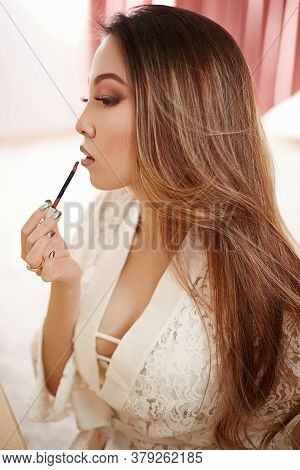 A Young Beautiful Asian Woman In A Beige Lace Dressing Gown Makes Morning Makeup And Puts Lipstick O