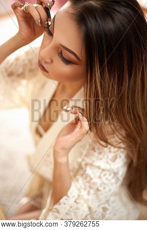 A Young Beautiful Asian Woman In A Beige Lace Robe Put On Morning Makeup And Uses Eye Shadow, Blush