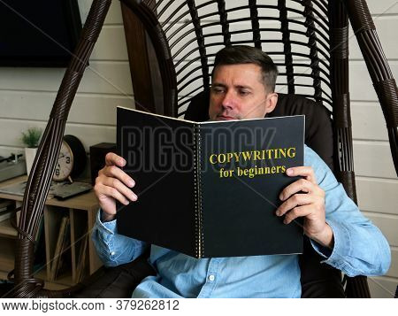 Copywriting For Beginners. A Man Is Reading A Guide At Home.