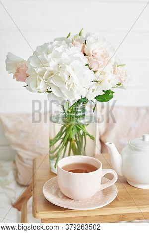 Breakfast In Bed In Hotel Room. Accommodation. Breakfast In Bed With Tea Cup And Flowers On Bed Back