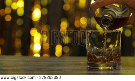 Barman Pouring Golden Whiskey, Cognac Or Brandy From Bottle Into Glass With Ice Cubes On Wooden Tabl