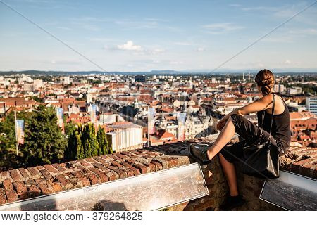 Graz, Austria - 13.07.2020: Woman Sitting On Red Wall Against Panorama View From The Top Of Schlossb