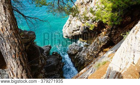 Aerial View On A Rocky Shore, Cliffs Closeup. Azure Water, Stormy Waves. Pine Branches