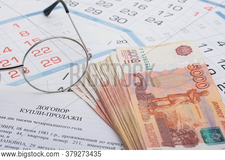Sale And Purchase Agreement Of An Apartment, A Wad Of Money, A Calendar And Glasses