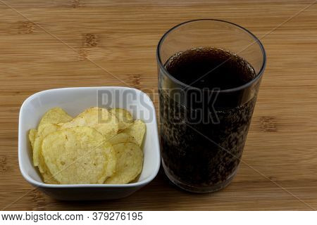 Soft Drink And Potato Crisps On A Wooden Surface