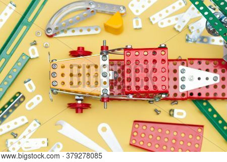 Metal, Iron Constructor On The Yellow Background. Parts Of Kids Metal Designer For Modeling.