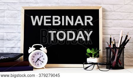 The Webinar Today Is Written On A Dark Wooden Board Next To An Alarm Clock, Black-framed Glasses, A