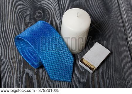 A Man's Tie And A Large White Candle. Beside A Box Of Matches. Love And Togetherness Objects. On Pai