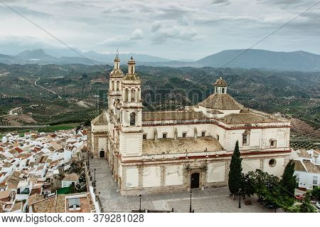 Church Of Our Lady Of Incarnation In Olvera, Andalusia, Spain. View Of The Church And Green Fields W