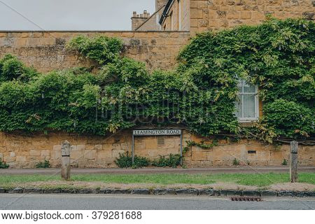 Leamington Road Street Name Sign Against The Limestone Cottage And Green Foliage In Broadway, Cotswo